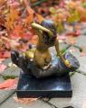 Бронзовая статуя женщины, сидящей на ладони