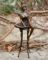 Статуя женщины на стуле из бронзы